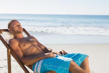 Handsome man on the beach having a nap while sunbathing on his deck chair photo