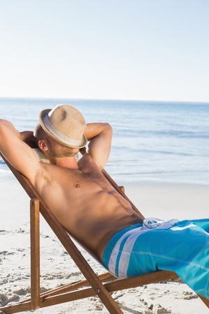 Handsome man on the beach sleeping with his hat covering his face  photo