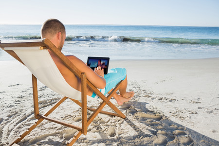 Handsome man scrolling on his tablet pc on the beach photo