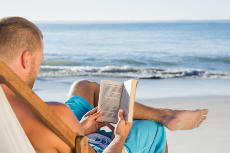 Handsome man reading a book on the beach photo