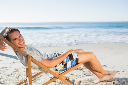 Handsome man on the beach lying on his deck chair smiling at camera photo