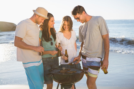 Cheerful young friends having barbecue together on the beach photo