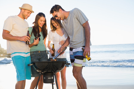 Smiling young friends having barbecue together on the beach photo