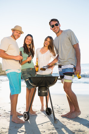 Happy friends on the beach looking at camera while having barbecue together photo