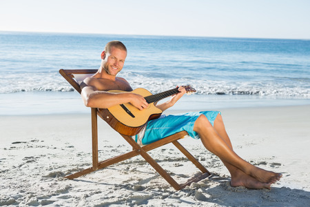 Cheerful handsome man playing guitar on the beach photo