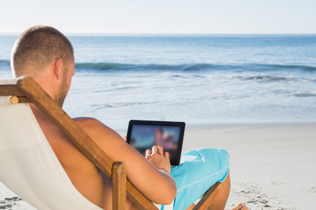 Handsome man on the beach scrolling on his tablet pc while sunbathing photo