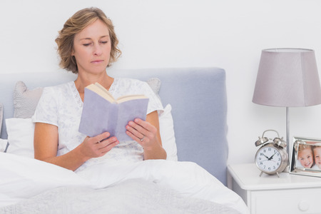 Relaxed blonde woman sitting in bed reading at home in bedroom photo