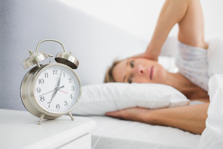 Blonde woman covering her ears from alarm clock noise in bed at home in bedroom photo