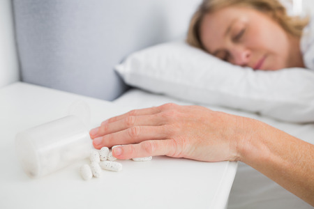 knocked over: Blonde woman lying motionless after overdose of medication at home in bedroom Stock Photo