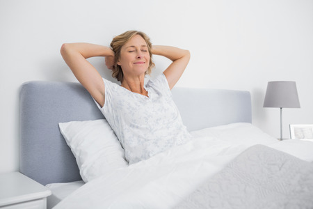 Blonde woman stretching and smiling in bed at home in bedroom