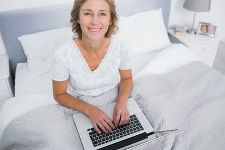 Smiling blonde woman in bed using her laptop looking at camera in bedroom at home photo