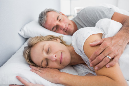 couple cuddling: Couple sleeping and spooning in bed in bedroom at home Stock Photo