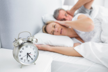 Couple covering their ears from alarm clock noise in bedroom at home