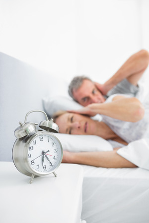 Couple blocking their ears from alarm clock noise in bedroom at home Stock Photo