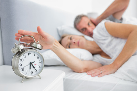 Wife turning off alarm clock as husband is covering ears in bedroom at home