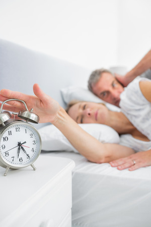 Tired wife turning off alarm clock as husband is covering ears in bedroom at home