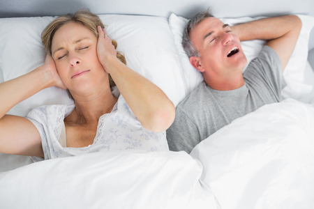 Wife blocking her ears from noise of husband snoring in bedroom at home photo