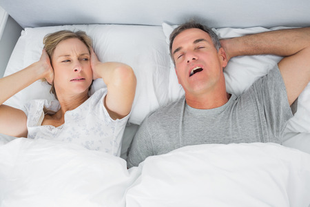 snoring: Annoyed wife blocking her ears from noise of husband snoring in bedroom at home