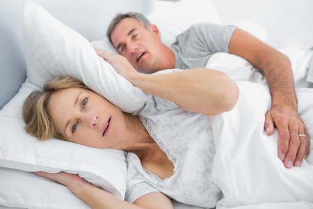 Irritated wife blocking her ears from noise of husband snoring in bedroom at home photo