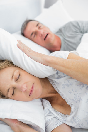 Tired wife blocking her ears from noise of husband snoring in bedroom at home