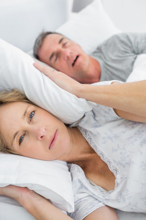 Tired wife blocking her ears from noise of husband snoring looking at camera in bedroom at home photo