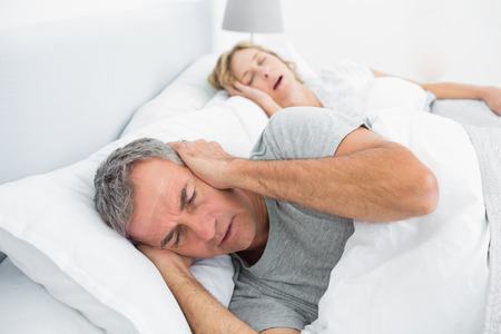 blocking: Tired man blocking his ears from noise of wife snoring in bedroom at home