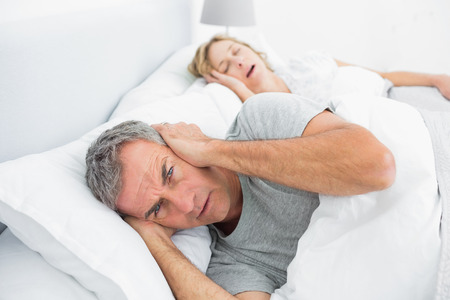 Annoyed man blocking his ears from noise of wife snoring at home in bedroom photo