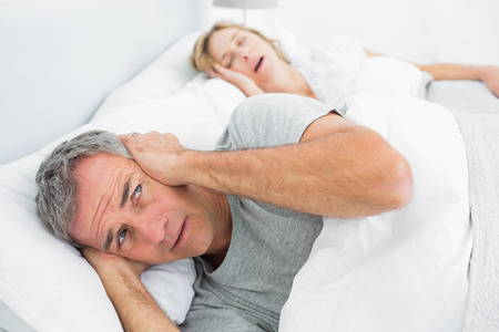 homely: Fed up man blocking his ears from noise of wife snoring at home in bedroom Stock Photo