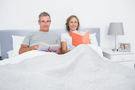 Cheerful couple sitting in bed reading books smiling at camera at home in bedroom photo