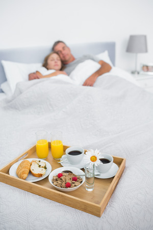 Cuddling couple sleeping with breakfast tray on bed at home in bedroom photo