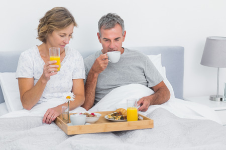 Happy couple having breakfast in bed together at home in bedroom photo
