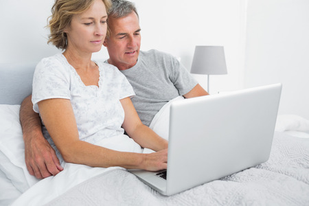 Happy couple using their laptop together in bed at home in bedroom photo
