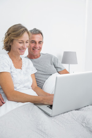 Cheerful couple using their laptop together in bed at home in bedroom photo