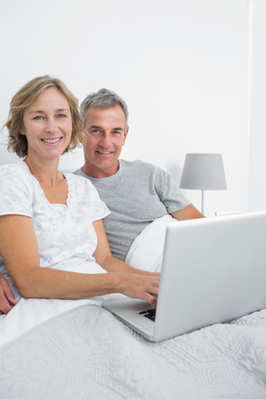 Middle aged couple using their laptop together in bed smiling at camera at home in bedroom photo