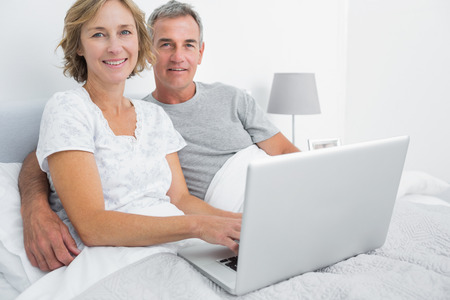 Relaxed couple using their laptop together in bed smiling at camera at home in bedroom photo
