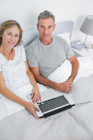 Couple using their laptop together in bed smiling at camera at home in bedroom photo