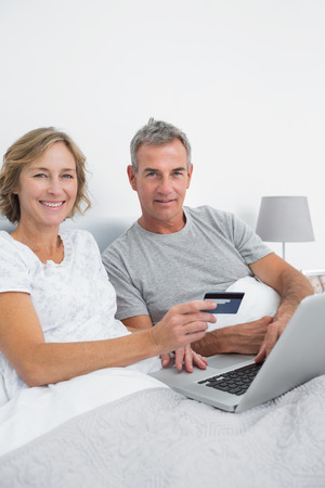 Happy couple using their laptop to buy online smiling at camera at home in bedroom photo