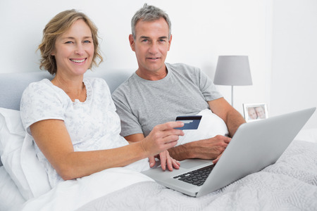 Smiling couple using their laptop to buy online in bed looking at camera at home in bedroom photo