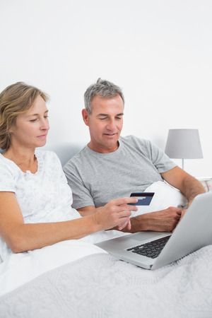 Cheerful couple using their laptop to buy online at home in bedroom photo