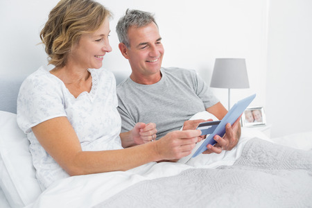 Cheerful couple using their tablet pc to buy online at home in bedroom photo