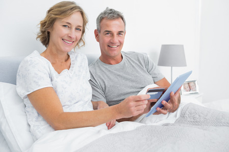 Happy couple using their tablet pc to buy online looking at camera at home in bedroom photo