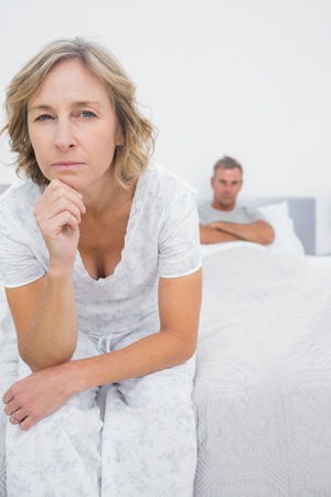 Annoyed woman looking at camera after fight with husband in bedroom at home photo