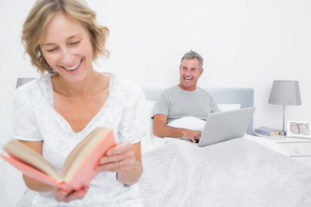 Woman reading book while husband is using laptop in bedroom at home photo
