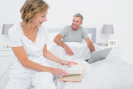 Smiling woman reading book while husband is using laptop in bedroom at home photo