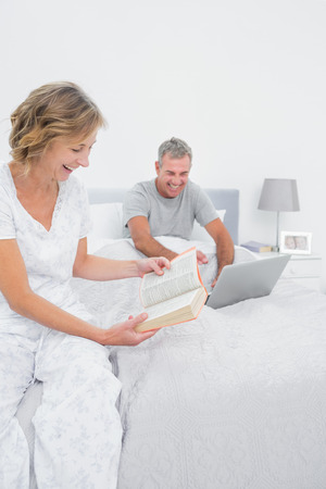 Happy woman reading book while husband is using laptop in bedroom at home photo