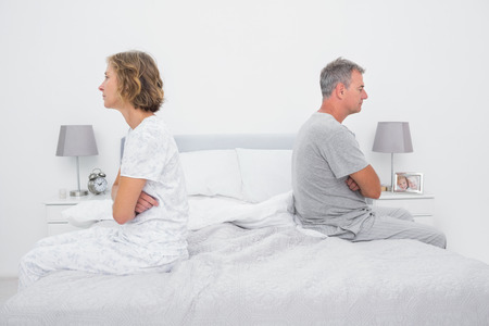 not talking: Couple sitting on different sides of bed not talking after dispute in bedroom at home