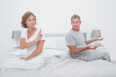 Couple sitting on different sides of bed having an argument in bedroom at home photo