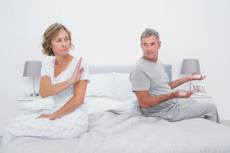 pareja discutiendo: Pareja sentada en diferentes lados de la cama teniendo una discusión en el dormitorio en casa