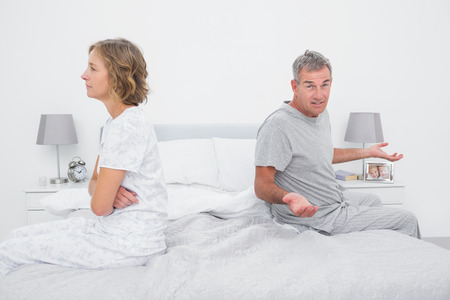 Couple sitting on different sides of bed having a dispute with husband gestruing at camera in bedroom at home photo