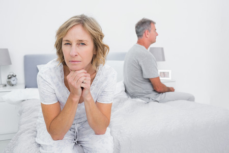 Thoughtful couple sitting on different sides of bed having a dispute with woman looking at camera in bedroom at home photo